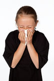 Teenage girl sneezes with a tissue isolated on white. Stock Image