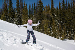 Teenage girl snowboarding down snowy hill in the mountains Stock Image