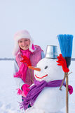 Teenage girl with snowman Royalty Free Stock Images