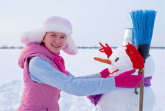 Teenage girl with snowman Royalty Free Stock Image