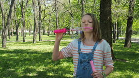 A teenage girl with soap bubbles in the park. Girl on a sunny day in the fresh air. A child is playing with bubbles in stock video