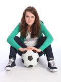 Teenage girl soccer player sits with football Stock Image
