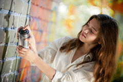Teenage girl with spray can makes graffiti Stock Image