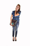 Teenage girl standing. An tall teenager with her notebook, in jean and a blue chickened blouse, standing for white background in the studio stock photos
