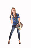 Teenage girl standing. An tall teenager with her notebook, in jean and a blue chickened blouse, standing for white background in the studio stock photo
