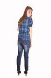 Teenage girl standing. An tall teenager with her notebook, in jean and a blue chickened blouse, standing for white background in the studio royalty free stock image