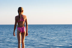 Teenage girl standing back turned face to sea stock photography