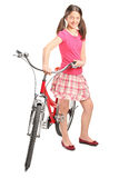 Teenage girl standing by a bicycle Stock Photography