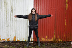 Teenage girl. Standing exact in the middle of a red white painted wall with outstretched arms Royalty Free Stock Photos
