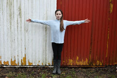 Teenage girl. Standing exact in the middle of a red white painted wall with outstretched arms Royalty Free Stock Images