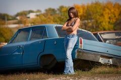 Teenage girl standing next to car. Young teenage girl looking at camera at salvage yard Royalty Free Stock Photography