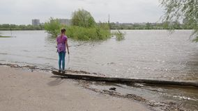 Girl happy spring and flood in the big city. A teenage girl standing swaying on a shattered tree thrown ashore at a flood. A young resident of the city rejoices stock video footage