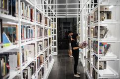 Bangkok - June 5,2017:The teenage girl is standing to read a book at white bookshelf at TCDC Library stock image