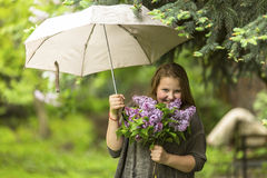 Teenage girl standing under an umbrella with a bouquet of lilacs in her hand. Happy. Stock Photos