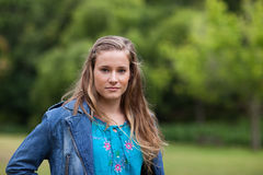 Teenage girl standing upright in a park. Teenager standing upright in a park while looking at camera Stock Image