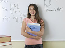 Teenage girl (15-17) standing beside whiteboard in classroom, holding textbook, smiling, portrait stock photography