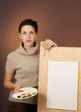 Teenage girl stands behind easel with empty sheet Royalty Free Stock Photos