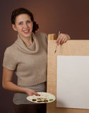 Teenage girl stands behind easel with empty sheet Stock Photos