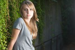 Teenage girl stands near vines in the shade facing right. Outside Stock Photography