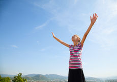 Teenage girl staying with raised hands. Against blue sky Royalty Free Stock Photos