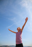 Teenage girl staying with raised hands Stock Photo