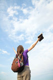 Teenage girl staying with raised hands. Against blue sky Stock Image