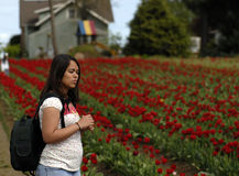 Teenage girl Stopping to smell the flowers. Royalty Free Stock Images