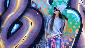 Teenage girl on the street. Teenager model with long hair wearing sunglasses and hat posing against a background of multi-colored wall, smiling stock video