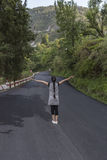 A teenage girl with stretched arm. S standing on the road Royalty Free Stock Image