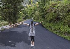 A teenage girl with stretched arm. S standing on the road Royalty Free Stock Photos