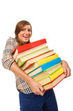 Teenage girl struggling with stack of books Royalty Free Stock Image