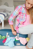 Teenage girl struggling to close suitcase Stock Image