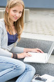Teenage girl study with laptop sitting stairs Royalty Free Stock Image