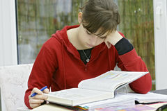 Teenage girl studying. A teenage girl sitting at a desk or table with several books in front of her, studying Stock Images
