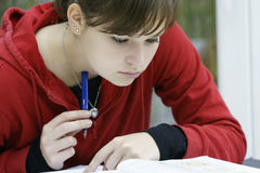 Teenage girl studying. A teenage girl sitting at a desk or table with several books in front of her, studying Royalty Free Stock Photography