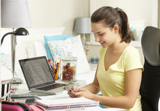 Teenage Girl Studying At Desk In Bedroom Using Mobile Phone Stock Photos