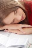 Teenage girl studying at the desk being tired Stock Images