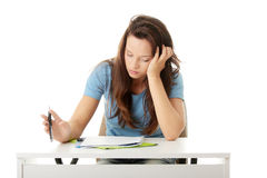 Teenage girl studying at the desk being tired Stock Photography
