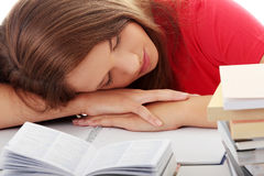 Teenage girl studying at the desk being tired Royalty Free Stock Image