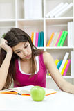 Teenage girl studying at the desk being tired Royalty Free Stock Photography