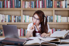 Teenage girl studying in the library Stock Photos