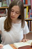 Teenage girl studying in a library. Student doing her homework in the school library stock images