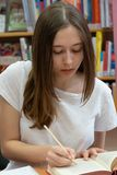 Teenage girl studying in a library. Student doing her homework in the school library stock photography