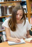 Teenage girl studying in a library. Student doing her homework in the school library royalty free stock photo