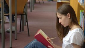 Teenage girl studying in the school library stock video footage