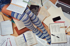 Teenage girl studying surrounded by textbooks, copybooks and oth. Teenage girl in tabby half-hoses and jeans shorts studying hard with her textbooks, copybooks royalty free stock image