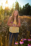 Teenage girl in a suburban or rural landscape. Teenage girl holding an coneflower flower on a suburban yard Royalty Free Stock Photos
