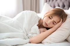 Teenage girl suffering from headache while lying in bed. At home Stock Photo