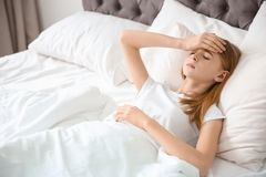 Teenage girl suffering from headache while lying. In bed at home Stock Image