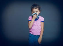 Teenage girl suffers a handkerchief on gray Royalty Free Stock Photography